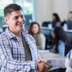 Confident Hispanic college professor greets student